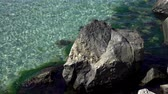 4K view of clear sea water near a rocky shore.