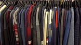 Fashionable collection of warm clothes. Various sweaters hang on hangers on the rack. HD video Dostupné videozáznamy