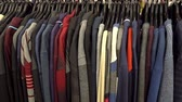 Fashionable collection of warm clothes. Various sweaters hang on hangers on the rack. HD video Vídeos