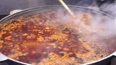 borscht : Cooks hand stirring vegetable soup. Street food large cauldron with hot soup.