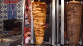 Cooking shawarma. Grossi spiedini di shawarma girano in cucina. Video HD