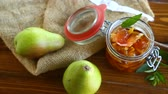 confiture : sweet fruit jam with apples and pears in a glass jar on a wooden table Stock Footage