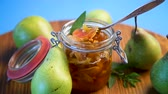 confiture : sweet fruit jam with apples and pears in a glass jar on a blue background Stock Footage