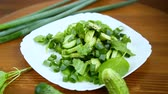 fruit : fresh salad of cucumbers and greens in a plate on a wooden