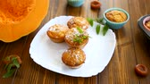 inclinar : baked sweet pumpkin muffins with dried apricots inside,