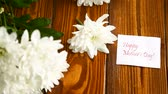 bouquet of white asters with a greeting card for mom Stock Footage