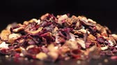 cherry : Pile of fruit tea with petals and dry fruit isolated on black, rotating