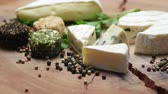 pimenta em grão : Varieties of cheese with herbs and peppercorns on a wooden board, rotating