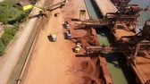 bauxite : TulceaRomania - May 23, 2018: Industrial cargo port with wheel loader loading ore on dump trucks, aerial view