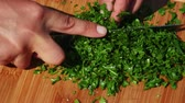 Chef chopping fresh parsley on a wooden board