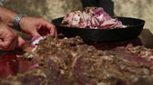 Farmer cutting (pastirma) air-dried spiced lamb meat into small pieces Stock Footage