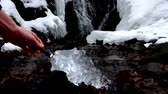 refração : Hand with strong flash light shinning into beautiful big piece of ice with cracks abstract. Fallen Icicle waterfall bellow, stony and messy stream banks