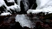 refração : Beautiful big piece of ice with cracks abstract. Fallen Icicle waterfall bellow, stony and messy stream banks