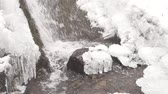 refração : Iciciles waterfall bellow. Snowy and icy stones and boulders with drops of fallen chilly water. Fallen Icicle waterfall bellow, stony and snowy stream banks. Close focus. Stock Footage