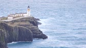 maritime territory : Beautiful sunrise on tenuously Point, thin spit of land with famous lighthouse at the end. West coast of the Isle of Skye in Scotland. Shinning lighthouse above sea of the Hebrides. Stock Footage