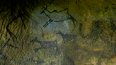 neanderthal : Discovery of prehistoric caveman hunt of paint in sandstone cave. Paint of human hunting of Deers, mammoth and reindeer. Spotlight shines on historical carbon black abstract art in sandstone cave Stock Footage