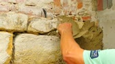 Close-up of a young man holding hands on a wall. Building stones and brick wall with mortar in construction site