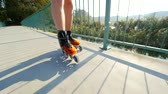 blading : Closeup of inline skating in hard shell skates. Sea bridge in sunny day Stock Footage