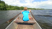 chaleco : Young teenage boy rowing and paddle boat on lake with forest at bank. Blue summer sky in the background
