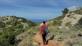 rood haar : Woman backpacker hiking during mountain trek on Mallorca islan. Sunny spring day with comfortable temperature. Rocky sandy footpath, pine trees, bushes and palms around.