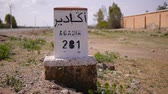 filho : Closeup of distance sign road to Agadir written in French and Arabic languages with carriding in the background. Morocco Stock Footage