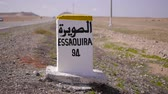 filho : Closeup of distance sign road to essaouira  written in French and Arabic languages with carriding in the background. Morocco Stock Footage