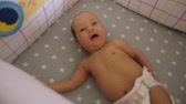 fralda : Top view of a child smiling in a baby bed. Handheld shot, camera changing focus