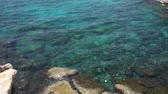 kıbrıs : Turquoise waving waters under the rocky cliff. Camera moves from stones below to horizon Stok Video