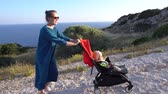 hillside : Young smiling woman pushes baby carriage up to a hill at sunny day. Handheld shot