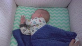 adormecido : Adorable baby sleeps in his bed. Female hands cover child with blue blanket. Top view, handheld shot