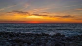 основной момент : Timelapse of bright orange sun setting into the Black Sea. Sunset on a pebble beach