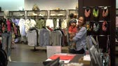 baby store : Laughing woman with a baby during clothing shopping at store. Handheld slow motion shot