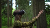 park entertainment : Woman tries to catch virtual objects playing with VR headsetin a forest Stock Footage