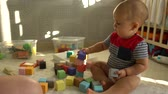 fralda : Cute toddler boy plays with colorful baby blocks sitting on a floor. Slow motion shot