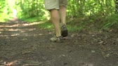 sandalet : Man walks on dirty track in a green park. Close up of legs in sport sandals