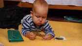 забавный : Serious baby boy plays with Euro banknotes lying on a floor