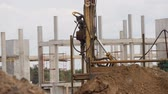 drilling site : Mobile drilling rig works at a building site. Concrete construction as a background Stock Footage