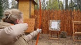 bowman : Blond woman shoots with red longbow and hits the target with arrow