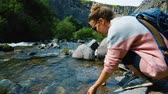 basalto : Young beautiful woman washes her hands in clear mountain river in Garni Gorge