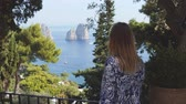 Long-haired woman among trees looks on Faraglioni sea stacks in blue sea. Capri, Italy