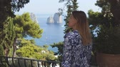 Woman points Faraglioni rock formations with the finger. View on sea from park. Capri, Italy