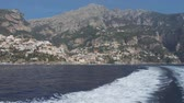 Motor boat floats away from the city on rocky slopes of coastal mountain. Positano, Italy
