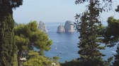 Faraglioni rocky sea stacks in blue sea. View from green park in Capri, Italy Stok Video