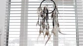 Dream protection amulet dreamcatcher of bird feathers hanging on the window with blinds in the morning, serene dreams talisman