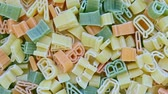 oleoso : Alphabet kids italian pasta of different colors close up texture rotation background
