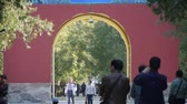wood : People walk in cypress trees park,China Beijing red door ancient buildings.