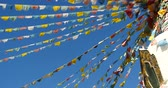 shangrila : 4k buddhist white stupa and flying prayer flags with blue sky background Stock Footage