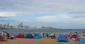 banho de sol :  many people at crowded bathing sandy beach.People swimming in sea,modern urban building background,QingDao,China. Vídeos