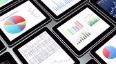 writing : Mobile devices,finance pie charts and stock trend diagrams in the tablet.
