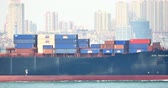 tariffs : 4k Cargo Container Ships Through The QingDao Harbo,moder urban building,china.